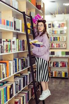 Devolvendo o livro. moça positiva de tênis branco encostada em uma escada preta enquanto carrega um monte de livros