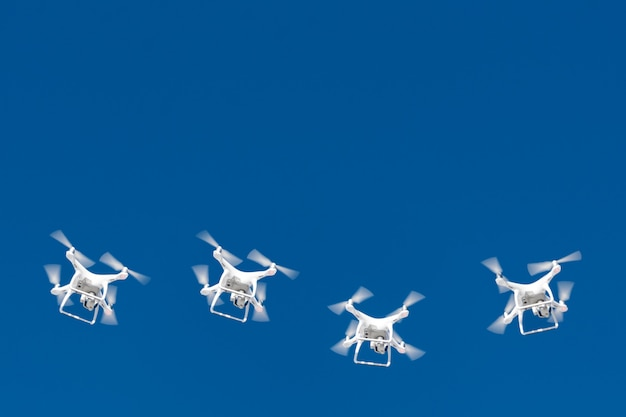 Dezenas de drones enxameiam no céu azul. quadcopters drones com câmera digital no ar sobre a cidade.