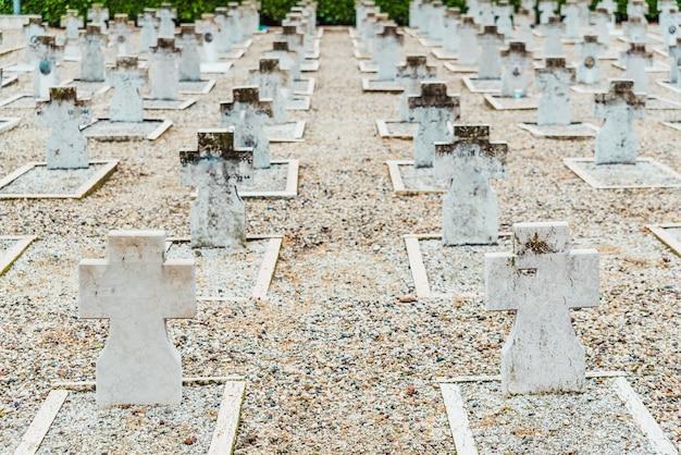 Dezenas de lápides de mármore em sepulturas brancas sem nome em um cemitério militar