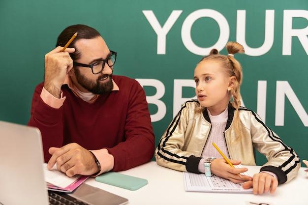 Dia agitado professor adulto barbudo, de cabelos escuros, usando óculos e seu aluno se sentindo ocupado enquanto trabalhava na aula