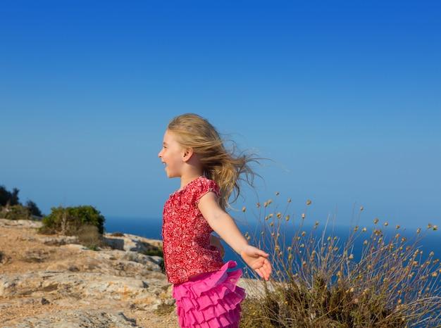 Dia azul com garota garoto abrir as mãos para o vento