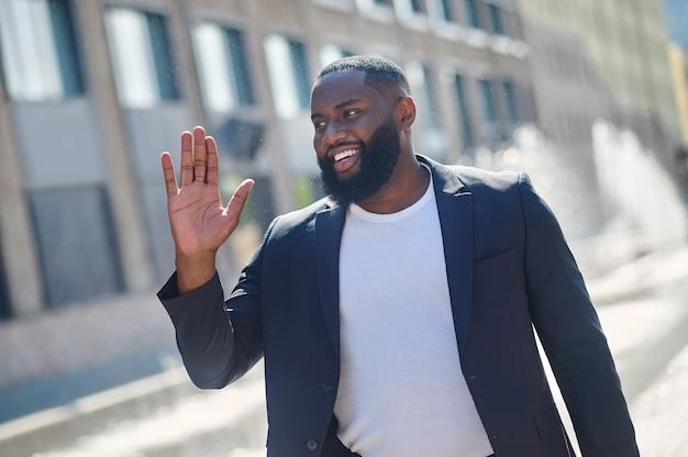 Dia bom. jovem afro-americano sorrindo e parecendo satisfeito
