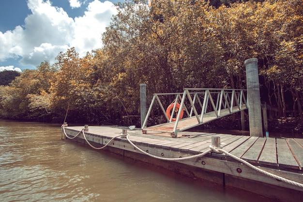 Dia brilhante com um pequeno cais no canal no parque nacional. viaje com a natureza nas florestas tropicais da tailândia.