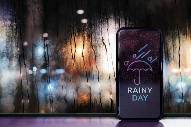 Dia chuvoso à noite no conceito de cidade. previsão do tempo via celular. gotas de chuva na janela de vidro. luzes urbanas borradas como vista externa