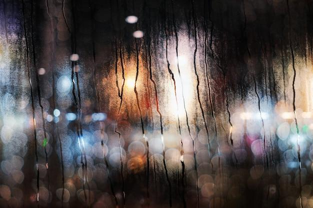 Dia chuvoso no conceito de cidade. pingos de chuva na janela de vidro. luzes urbanas desfocadas como vista externa