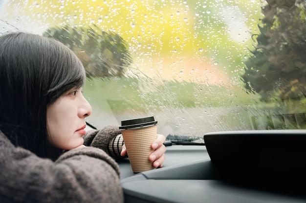 Dia chuvoso ou mau tempo em um conceito de férias. uma mulher de tristeza à espera de chuva para parar