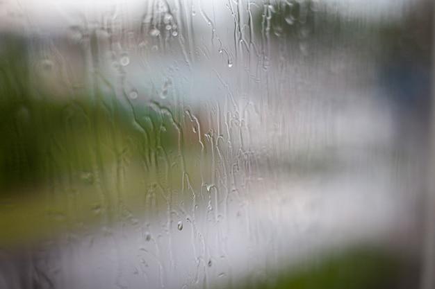 Dia chuvoso pela janela no céu nublado e cinza e fundo de edifícios da cidade. conceito. vista da cidade à noite atrás da janela de vidro com gotas de água escorrendo.