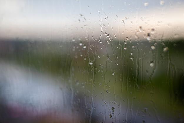 Dia chuvoso pela janela no fundo do céu e edifícios da cidade