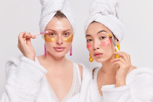 Dia da beleza e o conceito de cuidado de pele em casa. mulheres sérias com toalhas na cabeça após o banho usam escovas cosméticas e aplicam adesivos sob os olhos para hidratar