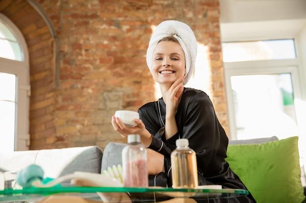 Dia da beleza. mulher com roupão de seda, fazendo sua rotina diária de cuidados com a pele em casa. parece satisfeita, passando hidratante na pele do rosto, sorrindo. conceito de beleza, autocuidado, cosméticos, juventude.