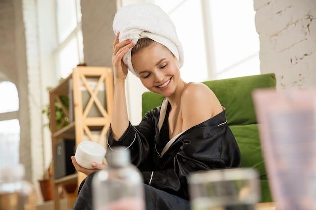 Dia da beleza. mulher com roupão de seda, fazendo sua rotina diária de cuidados com a pele em casa. parece satisfeita, passando hidratante na pele dos ombros, sorrindo. conceito de beleza, autocuidado, cosméticos, juventude.
