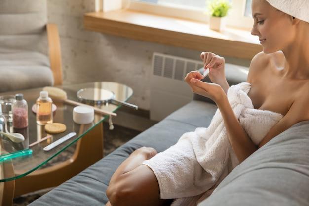 Dia da beleza mulher usando toalha fazendo sua rotina diária de cuidados com a pele e manicure em casa