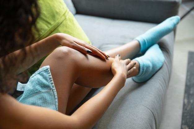 Dia da beleza. perto de mulher usando toalha, fazendo sua rotina diária de cuidados com a pele em casa. sentado no sofá, passando hidratante e massageando a pele das pernas. conceito de beleza, autocuidado, cosméticos, juventude.