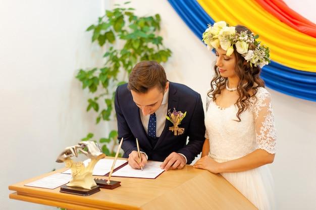 Dia da cerimônia, esposa e marido no escritório civil de registro