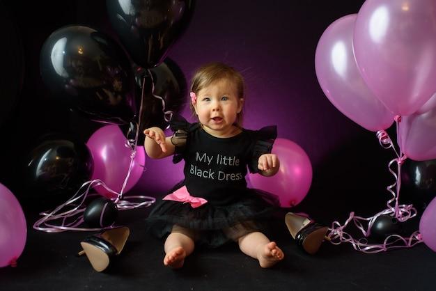Dia da festa de aniversário do primeiro ano do bebê. balões e férias dentro de casa. aniversário da criança. menina bonita em seu primeiro vestido preto