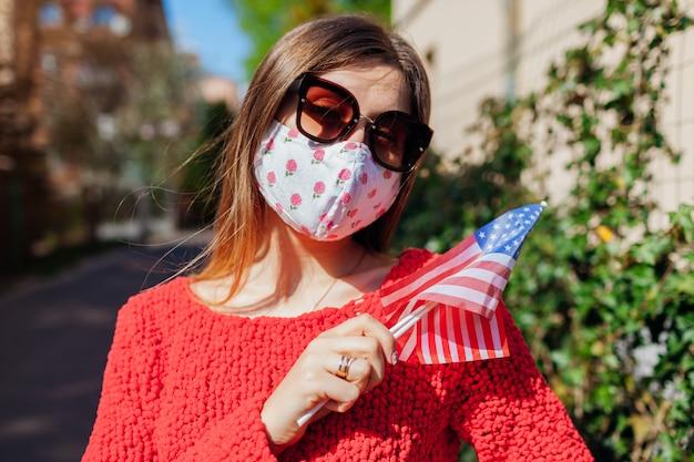 Dia da independência dos eua. a mulher veste a máscara protetora ao ar livre prende bandeiras durante o coronavírus covid-19.