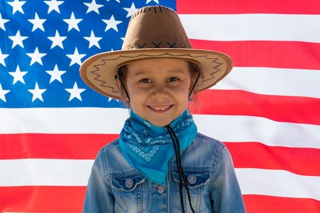 Dia da independência. feriado patriótico. criança feliz, menina criança bonitinha com bandeira americana. vaqueiro. eua celebram 4 de julho.