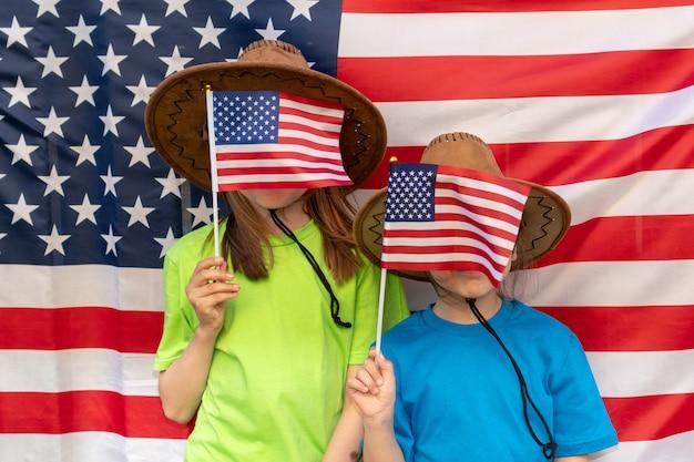 Dia da independência. feriado patriótico. crianças felizes, lindas duas garotas com bandeira americana. vaqueiro. eua celebram 4 de julho. meninas cobrem o rosto com bandeiras