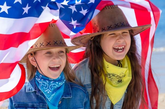 Dia da independência. feriado patriótico. crianças felizes, lindas duas garotas com bandeira americana. vaqueiro. eua comemoram 4 de julho