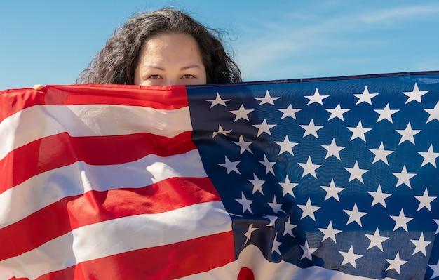 Dia da independência. feriado patriótico. uma mulher com cabelo preto encaracolado está segurando uma bandeira americana. o conceito de paz mundial. eua celebram 4 de julho.