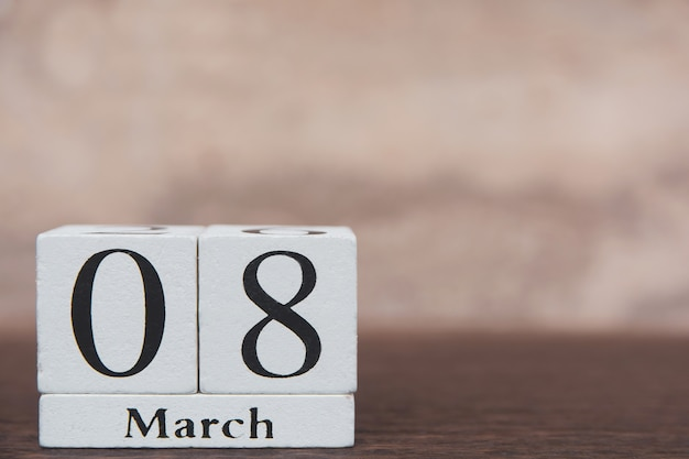 Dia da mulher com cubo de bloco de madeira de calendário de 8 de março com número na prancha de mesa escura de madeira com espaço de cópia