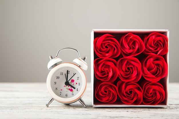 Dia da mulher, dia das mães, rosas vermelhas e um relógio em um fundo branco de madeira.
