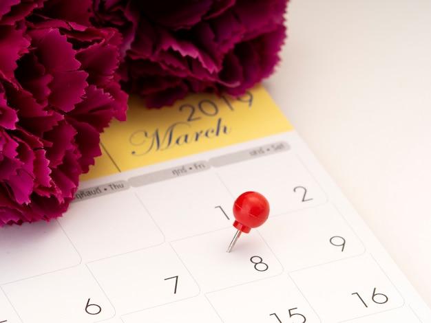 Dia da mulher no calendário com o pino vermelho.