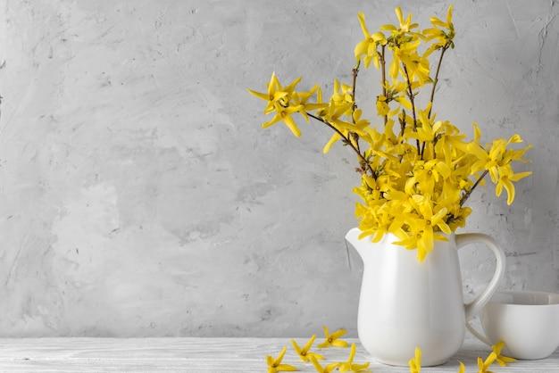 Dia da mulher ou conceito de primavera. natureza morta com flores amarelas de forsítia e xícara de café
