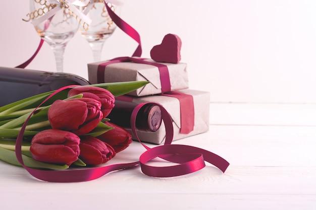 Dia da mulher. presentes com flores e vinho na parede branca