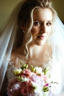 Dia da noiva. noiva linda no vestido de casamento branco com bouquet de noiva na manhã do casamento.