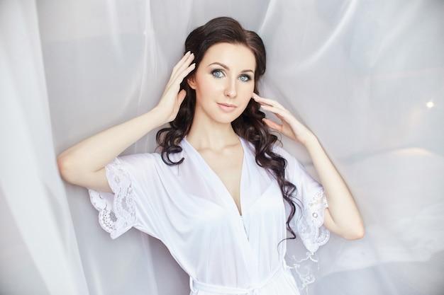 Dia da noiva, uma garota com um roupão de seda em pé perto da janela contra as cortinas brancas