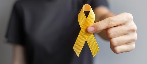 Dia da prevenção do suicídio, mês da conscientização do câncer de osso, bexiga e infância, sarcoma, fita amarela para apoio a pessoas que vivem e adoecem. conceito de saúde infantil e dia mundial do câncer