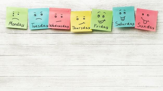 Dia da semana e expressão facial. adesivos coloridos em uma luz de madeira