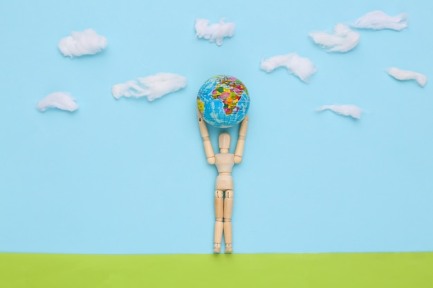Dia da terra. boneco de madeira segura o planeta terra em um campo feito à mão no céu azul com nuvens
