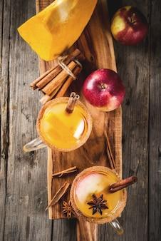 Dia das bruxas, ação de graças. outono tradicional, bebidas de inverno e coquetéis. sangria de abóbora quente picante, com maçã, canela, anis. na velha mesa de madeira rústica, em canecas de vidro. espaço de cópia da vista superior