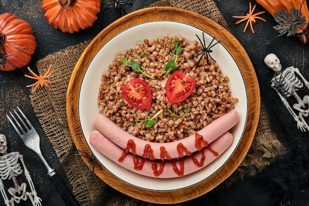 Dia das bruxas comida arte ideia almoço saudável para crianças. mingau de trigo sarraceno cozido, linguiça de carne, tomate e microgreens de ervilhas