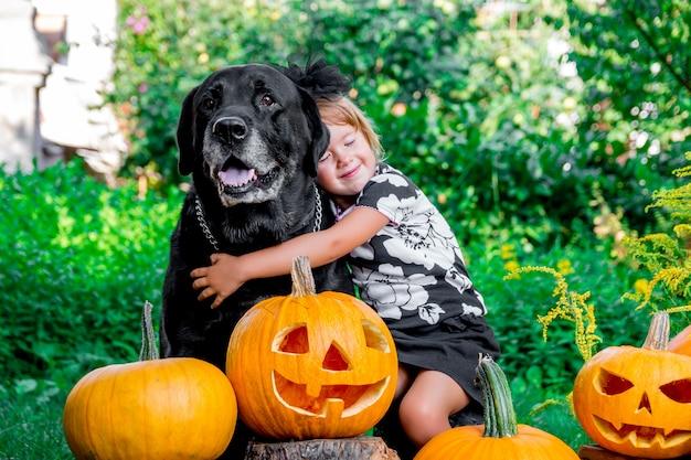 Dia das bruxas. criança vestida de preto perto de labrador entre decoração jack-o-lanterna, gostosuras ou travessuras.