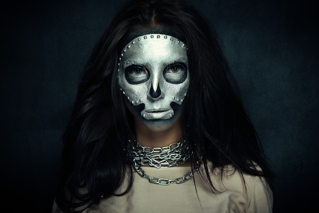 Dia das bruxas, feriados, estilo de vida, pessoas, beleza, conceito criativo - tema de halloween e maquiagem criativa: modelo de menina bonita com corpo preto com máscara prateada pintura do crânio em fundo escuro no estúdio