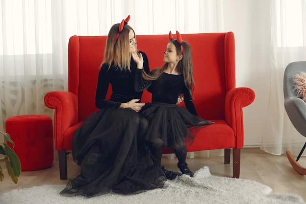Dia das bruxas. mãe e filha com fantasia de halloween. família em casa.