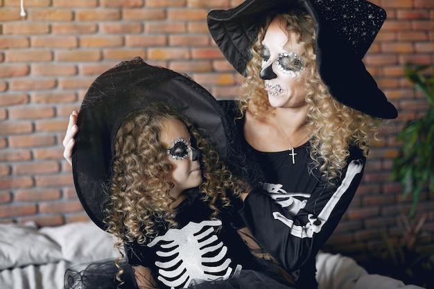 Dia das bruxas. mãe e filha em traje de halloween de estilo mexicano. família em casa.