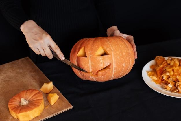 Dia das bruxas. mãos de menina com uma faca cortando abóbora laranja para fazer lanterna de jack