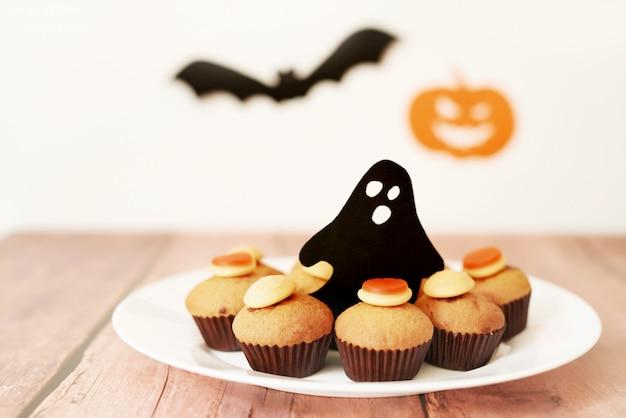Dia das bruxas trata cupcakes na mesa contra o fundo de abóboras e morcegos