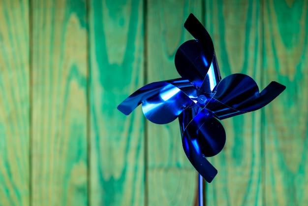 Dia das crianças. cata-vento azul metálico sobre fundo verde de madeira
