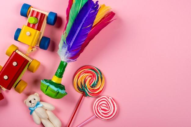 Dia das crianças. trem de madeira, peteca, urso de pelúcia, pirulitos sobre fundo rosa neon