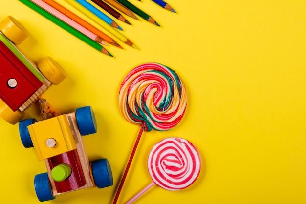 Dia das crianças. trem de madeira, pirulito e lápis de cor sobre fundo amarelo
