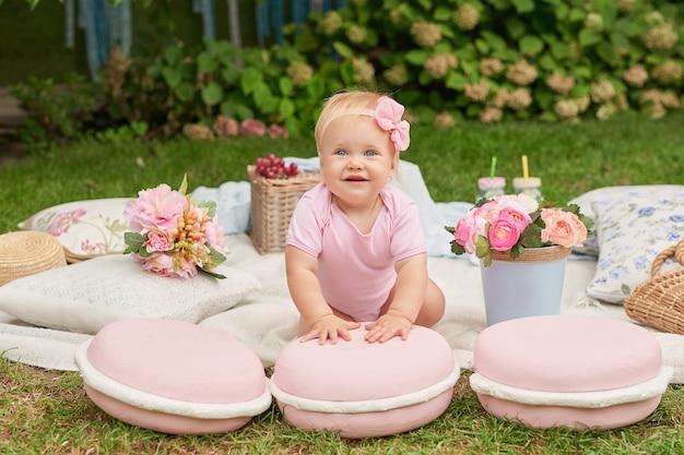 Dia das crianças, uma menina criança no parque senta-se em uma cesta com biscoitos em um piquenique de verão