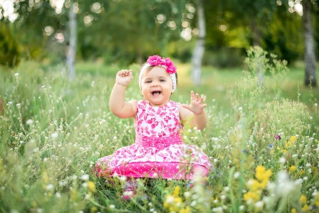 Dia das crianças, uma menina no parque no verão, sentado na grama