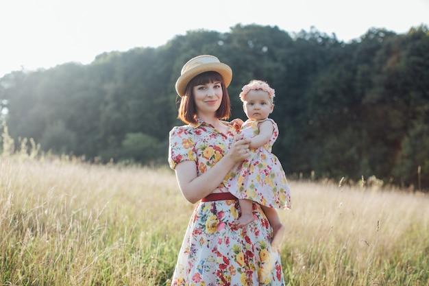 Dia das mães. conceito de família. jovem muito sorridente mãe de vestido e chapéu de palha, segurando o bebê. mãe e filha se divertindo no campo de verão, posando para a câmera