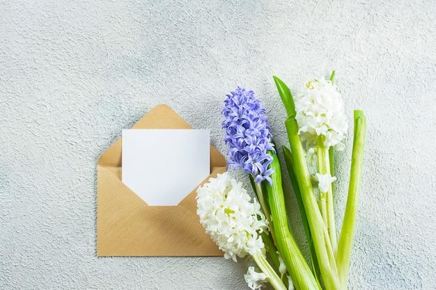 Dia das mães conceito de férias. jacintos flores e cartão vazio sobre fundo claro de concreto. cartão de primavera. configuração plana, vista superior, copie o espaço ..
