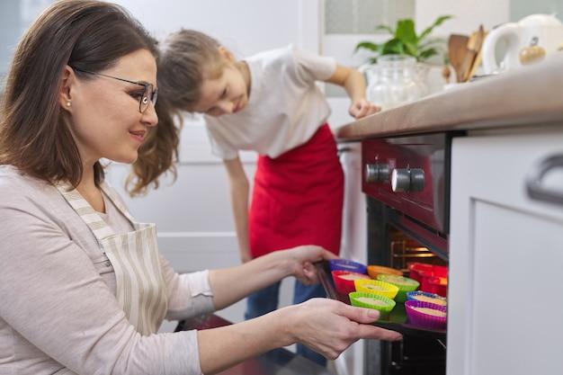 Dia das mães, criança mãe e filha preparando cupcakes em casa na cozinha, mulher ensinando criança a cozinhar